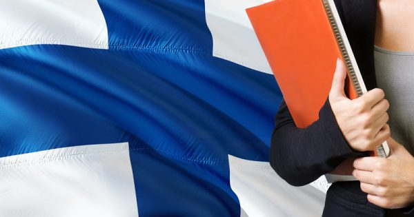Learning Finnish language concept. Young woman standing with the Finland flag in the background. Teacher holding books, orange blank book cover.