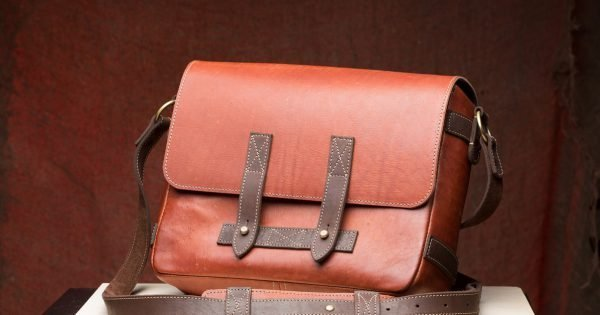 Old vintage leather bag with leather strap on wooden table