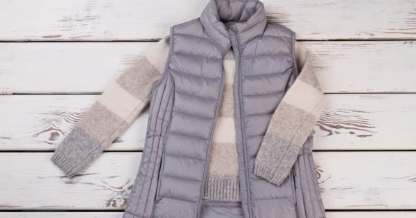 Combination of vest and sweater for chill autumn weather. New collection items on a wooden shelf.