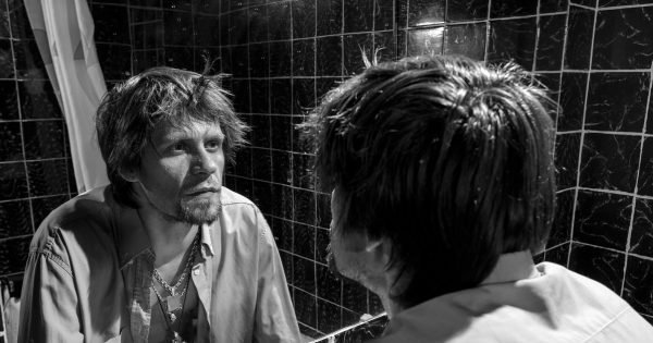 Drunk Man looks at himself in the mirror in a bathroom. grayscale image