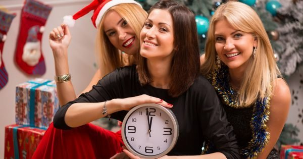 Selective focus on the three happy friends wearing fancy dress sitting and hugging each other near the Christmas tree holding a big clock that shows New Year is coming