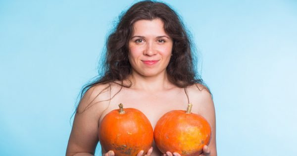 Young happy woman holds pumpkin in hands above her breast. Plastic surgery and silicone implants concept