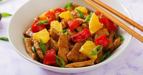 Veal fillet - stir fry with oranges and paprika in sweet and sour sauce on a light background