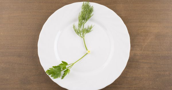 plate with green grass with dill and  fennel  in the form of dial,  on white brown wooden texuted table