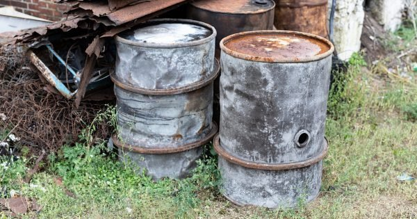 Old barrels for diesel. Metal containers for oil standing on the scrap yard. Season of the autumn.